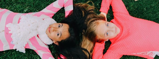Young Girls Laying on Grass 1280x480